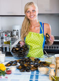 Woman cooking marinade for tasty mussels at kitchen table Stock Photos