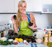 Woman cooking marinade for tasty mussels at kitchen table Royalty Free Stock Image