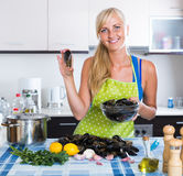 Woman cooking marinade for tasty mussels at kitchen table Royalty Free Stock Photo