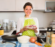 Woman cooking meat with rice Royalty Free Stock Images