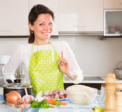 Woman cooking meat with rice and smiling Royalty Free Stock Photo