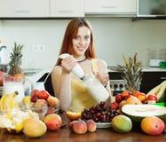 Woman cooking milkshake with fruits Stock Image