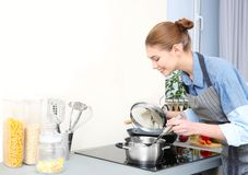 Woman cooking on modern stove royalty free stock images