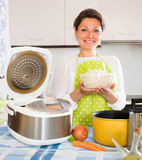 Woman cooking with multicooker at home Stock Photos