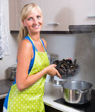 Woman cooking mussels at home Stock Photo