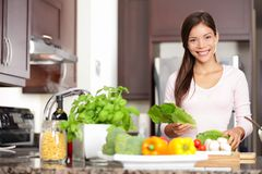 Woman cooking in new kitchen. Making healthy food with vegetables. Young multicultural Caucasian / Asian Chinese woman in her twenties Royalty Free Stock Image