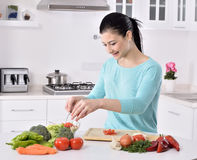 Woman cooking in new kitchen making healthy food with vegetables. Royalty Free Stock Images