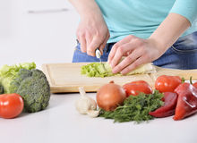 Woman cooking in new kitchen making healthy food with vegetables. Stock Photo