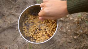 Woman cooking noodle soup on a camping gas stove outdoors. 4K stock video