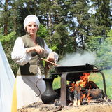 Woman cooking on opened fire Royalty Free Stock Photography