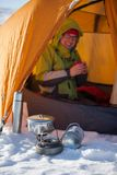 Woman cooking outside tent in wintertime in nature Stock Images