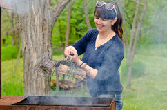 Woman cooking over a BBQ reacting in horror Royalty Free Stock Photo