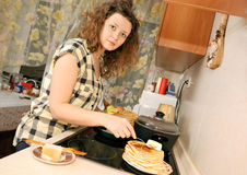 Woman cooking pancakes Stock Images