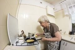 Woman cooking a pancakes at home. Royalty Free Stock Photos