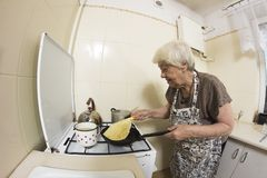 Woman cooking a pancakes at home. Stock Photos