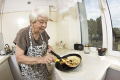 Woman cooking a pancakes at home. Royalty Free Stock Photography