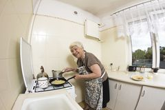 Woman cooking a pancakes at home. Stock Images