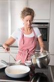 Woman cooking pancakes Stock Photos