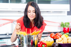 Woman cooking pasta in kitchen Stock Photo