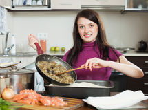 Woman cooking  pie with salmon and vegetables Royalty Free Stock Photo