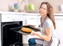 Woman Cooking Pizza. Happy Young Woman Cooking Pizza at Home Royalty Free Stock Image