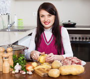 Woman cooking potatoes with  meat Stock Photos