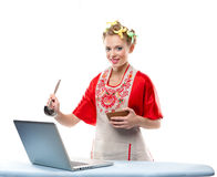 Woman is cooking with the recipe on a laptop Royalty Free Stock Photos
