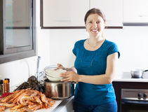 Woman cooking rice with sea foods. Happy woman cooking rice with sea foods in kitchen Royalty Free Stock Images