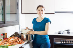 Woman cooking rice with seafoods. Happy woman cooking rice with seafoods in kitchen Royalty Free Stock Photography