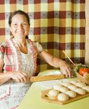 Woman cooking with rolling pin Royalty Free Stock Photo