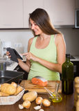 Woman cooking salmon with ereader Royalty Free Stock Photography