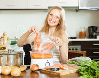 Woman cooking salmon fish and vegetables Stock Images