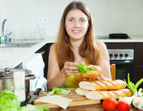 Woman cooking sandwiches with vegetables. In her kitchen Royalty Free Stock Photo