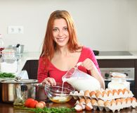 Woman cooking scrambled eggs in home kitchen Royalty Free Stock Images