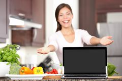 Woman cooking showing laptop in kitchen. Woman showing laptop cooking in kitchen. Focus on screen with copy space. Excited mixed race asian caucasian young woman royalty free stock images