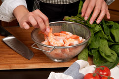Woman cooking shrimps in the kitchen Royalty Free Stock Photography