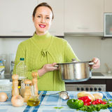 Woman cooking soup in kitchen Stock Image