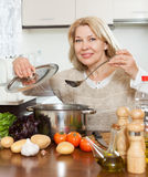 Woman cooking  soup in kitchen Stock Photo