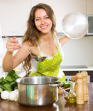 Woman cooking soup in kitchen Royalty Free Stock Photo