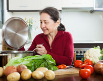 Woman cooking  with  soup ladle in domestic kitchen Royalty Free Stock Photo