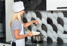 A woman is cooking spaghetti and sausages. A woman is cooking stock photos