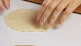 Woman cooking and spreading a dough with rolling pin. White kitchen table stock video