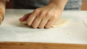 Woman cooking and spreading dough. Width wooden rolling pin on a white table in the kitchen stock footage