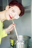 Woman cooking with steam on her glasses Stock Photography