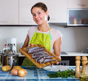 Woman cooking stew with sardines Royalty Free Stock Images