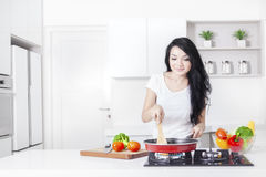 Woman cooking on the stove with frying royalty free stock images