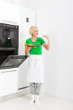 Woman cooking taste cookies, baking taking from. Oven tray, young smile girl modern kitchen at home Royalty Free Stock Photography