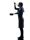 Woman cooking tasting saucepan silhouette Stock Image