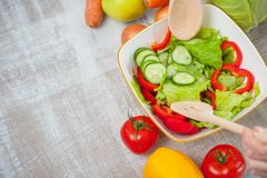 Woman is cooking tasty fresh salad and mingling it Stock Photo