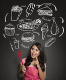 Woman cooking thinking what to cook. Woman holding cooking spatula and thinking what to cook Royalty Free Stock Photos